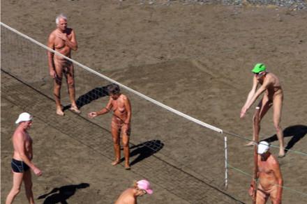 """En gjeng eldre menn og kvinner spiller nakenvolleyball på stranda. Tittel øverst på bildet: """"Ja vi"""