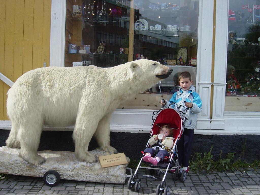 Barn poserer ved en utstoppet isbjørn i Tromsø.