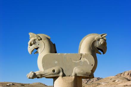 Detalj fra ruinene av perserhovedstaden Persepolis: To griffer mot himmelen i horisonten.